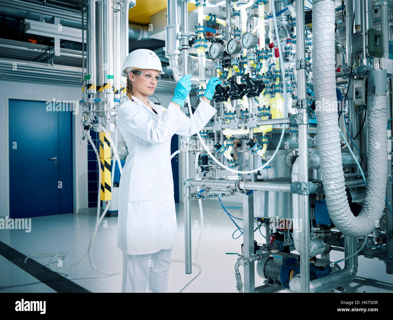 Chemielaborantin, chemist with helmet and goggles in a pharmaceutical production, Austria - Stock Image