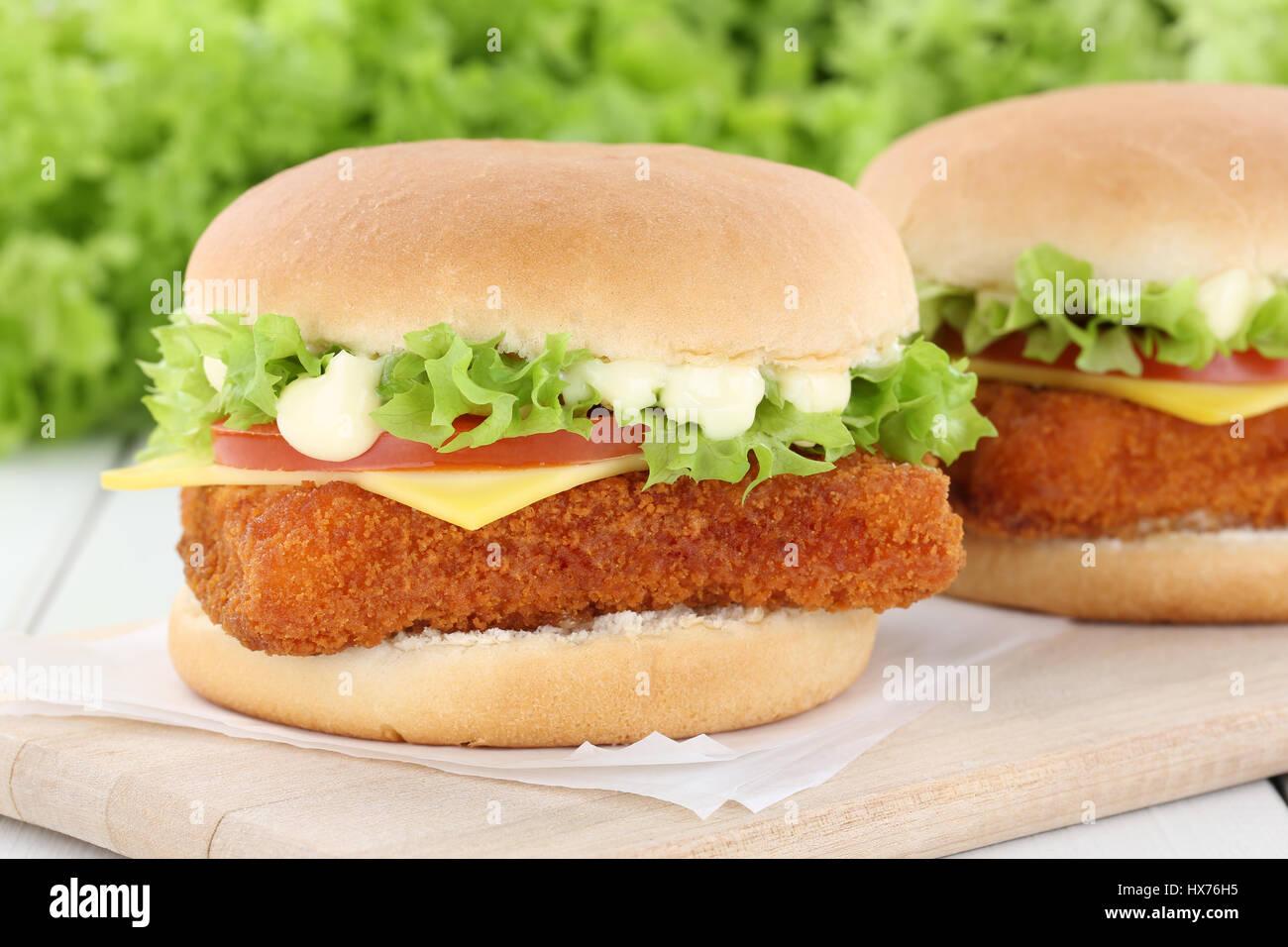 Fish burger fishburger hamburger tomatoes cheese unhealthy eating - Stock Image