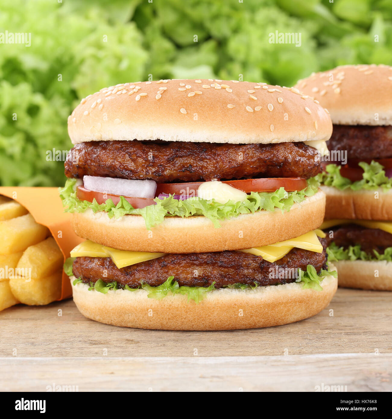 Double burger hamburger and fries tomatoes lettuce fast food - Stock Image
