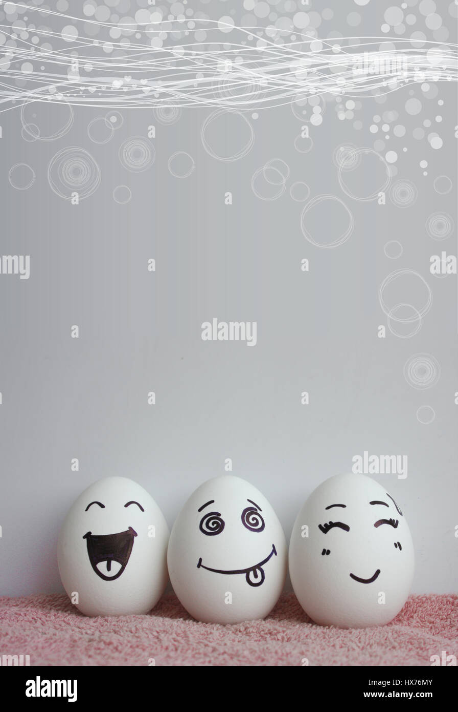Three eggs on pink with cheerful faces vertical. A photo with a place under the text for your design Stock Photo