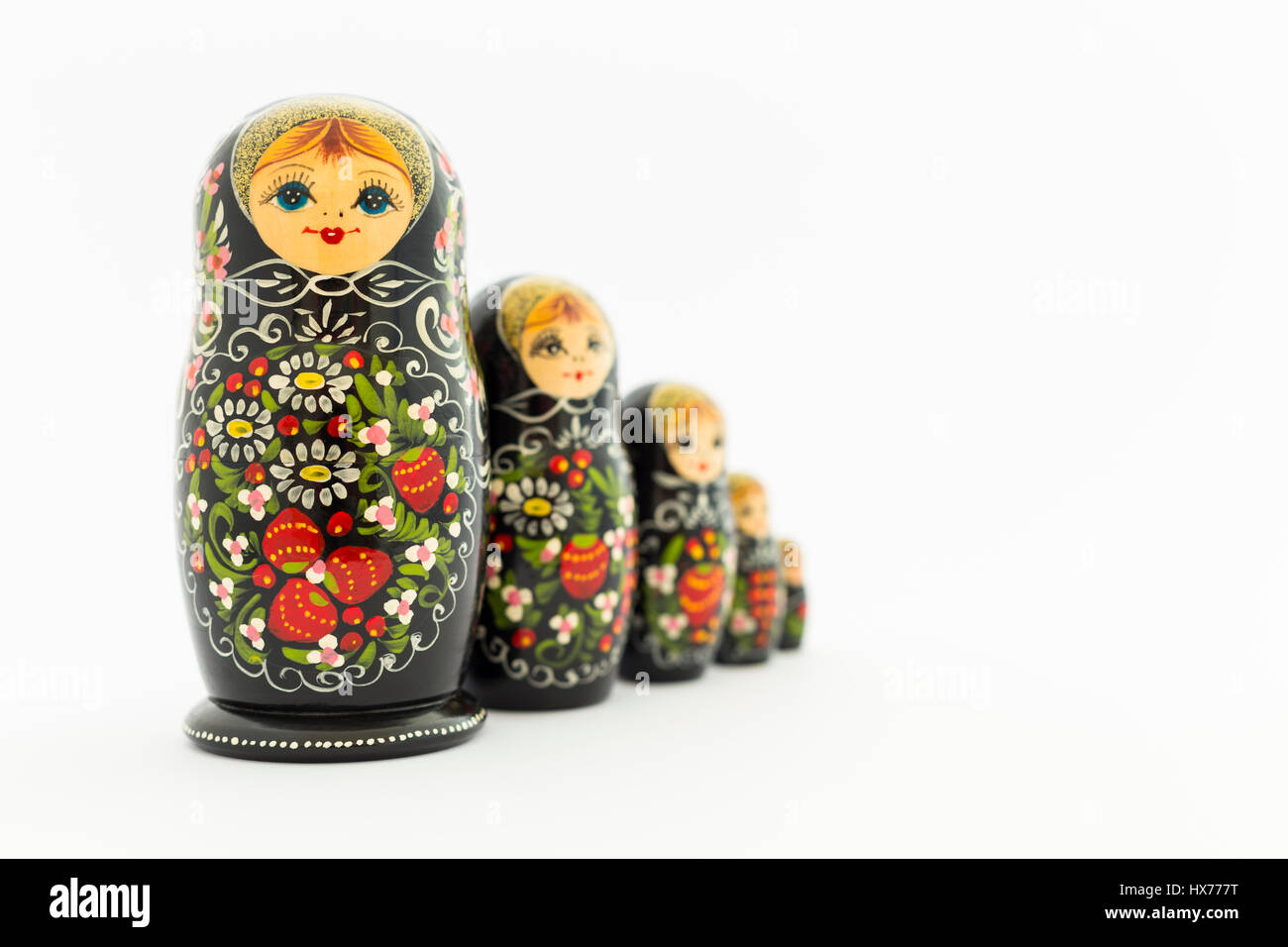 Beautiful black russian nesting dolls (matryoshka dolls) with white, green and red painting in front of white background - Stock Image
