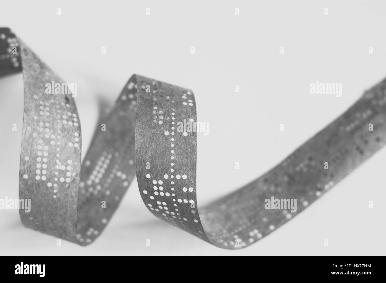 Strips of old punched tape on white surface - Stock Image
