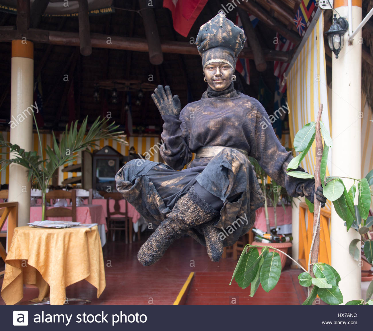 Levitating woman trick at the entrance of restaurant 'El Rancho'.  The trick make tourists stop for a while - Stock Image