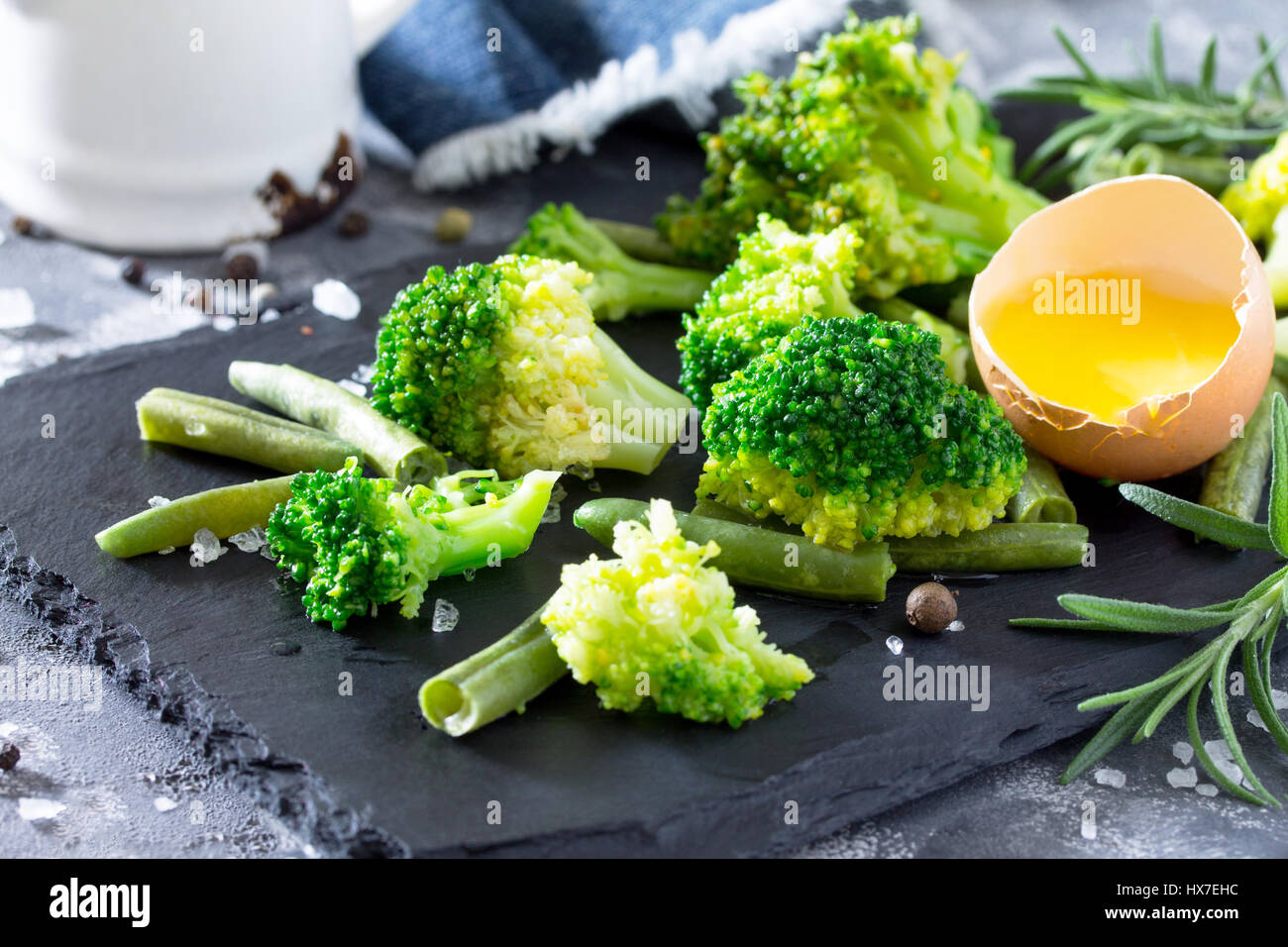 Fresh green broccoli, green beans, milk, rosemary and eggs on a slate. The concept of healthy and dietary nutrition. - Stock Image