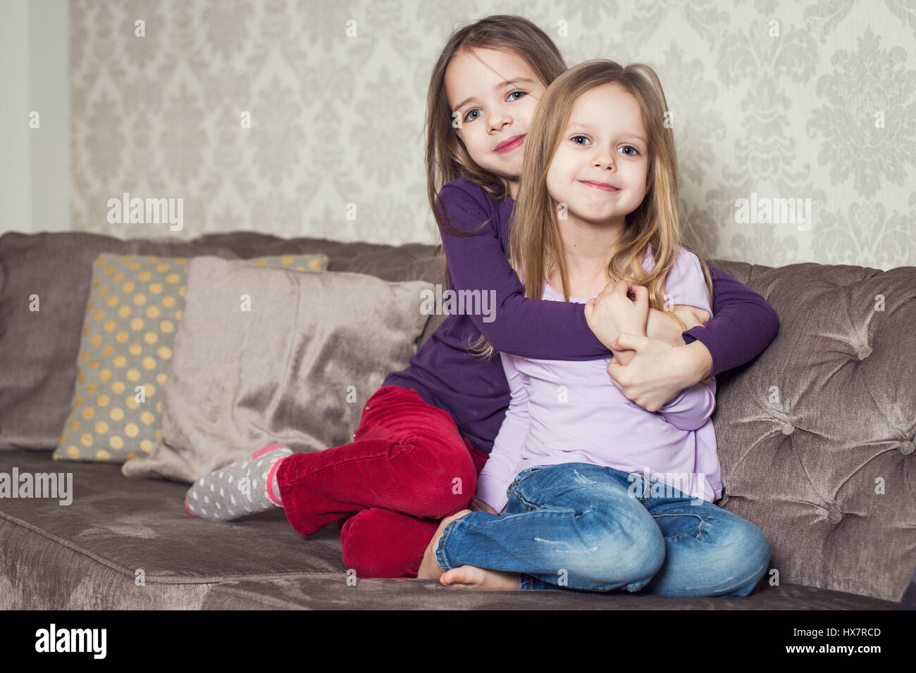 Portrait of two cute sisters at home. Family. Indoor lifestyle portrait of couple beautiful sisters best friends. - Stock Image