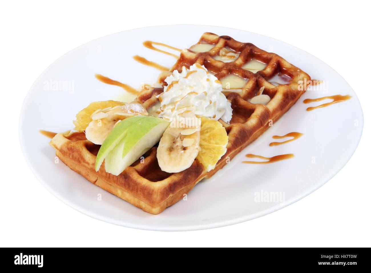 Dessert dish, Belgian waffle with condensed milk, whipped cream and slices of fruit, banana, apple, orange, put - Stock Image
