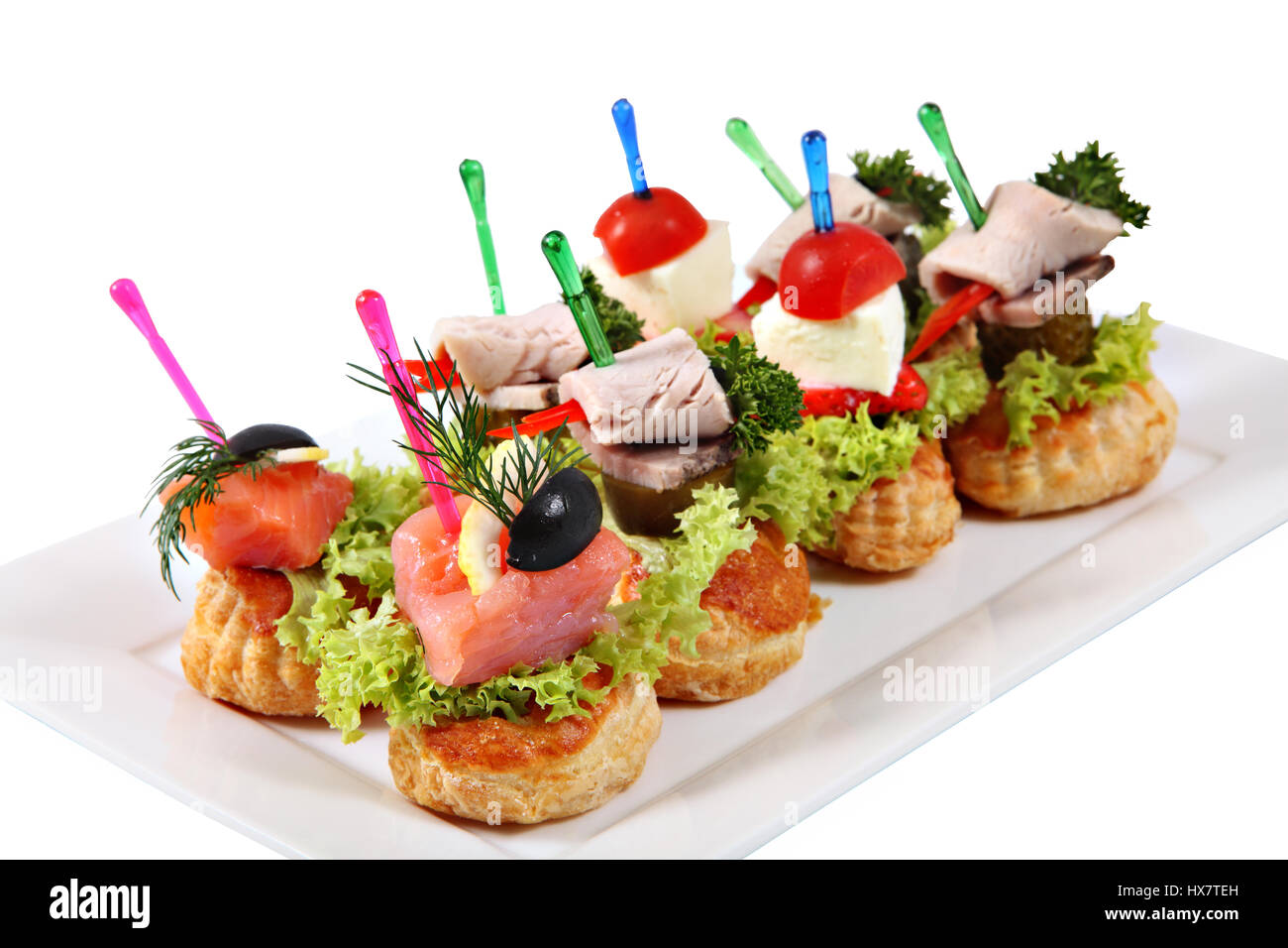 Many small canape sandwiches on colored plastic skewers put on a plate isolated on a white background.  sc 1 st  Alamy & Many small canape sandwiches on colored plastic skewers put on a ...