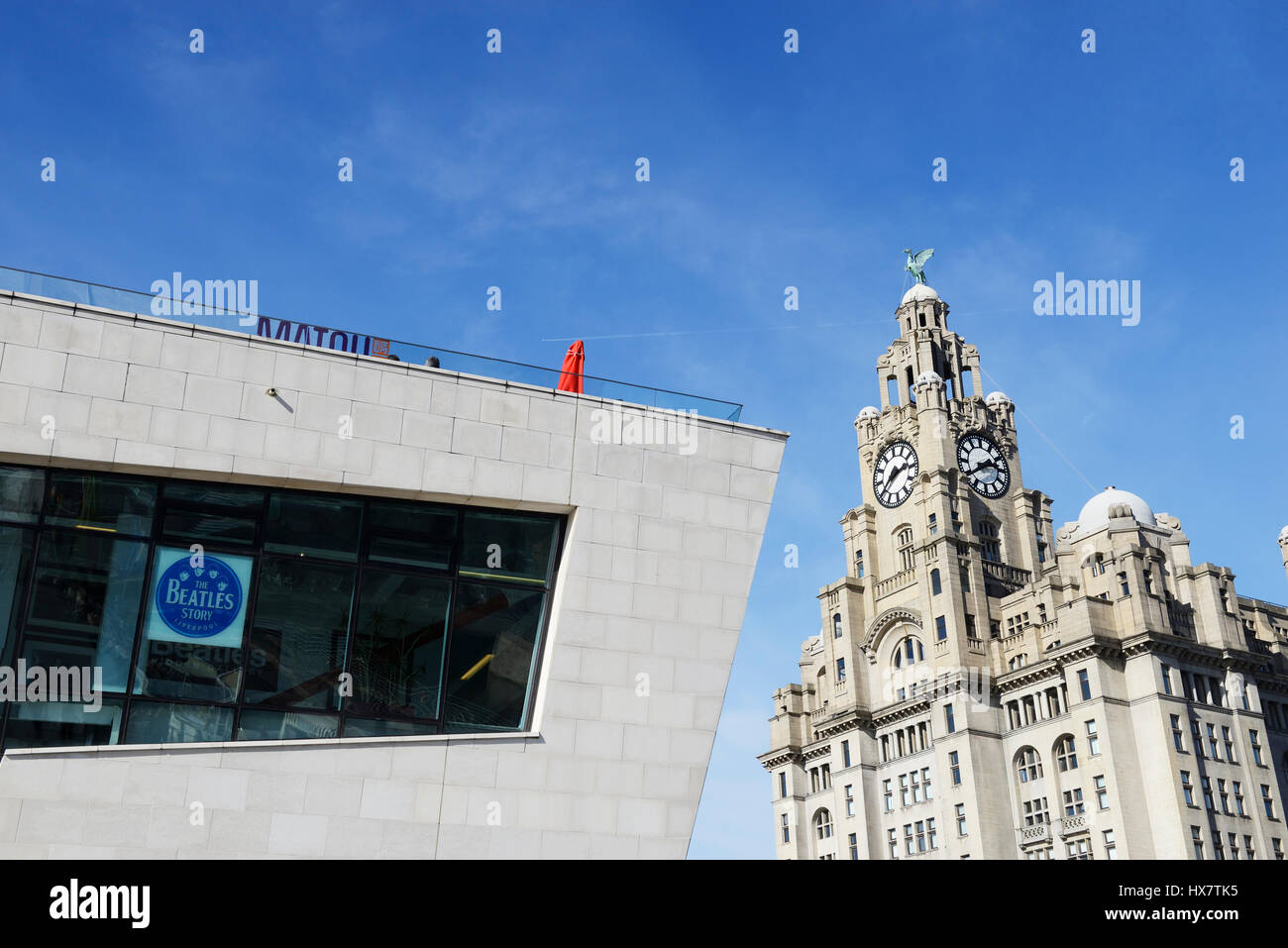 The Beatles Story, a tourist attraction within the New Mersey Ferries building at Pier Head with iconic Liver Building. - Stock Image