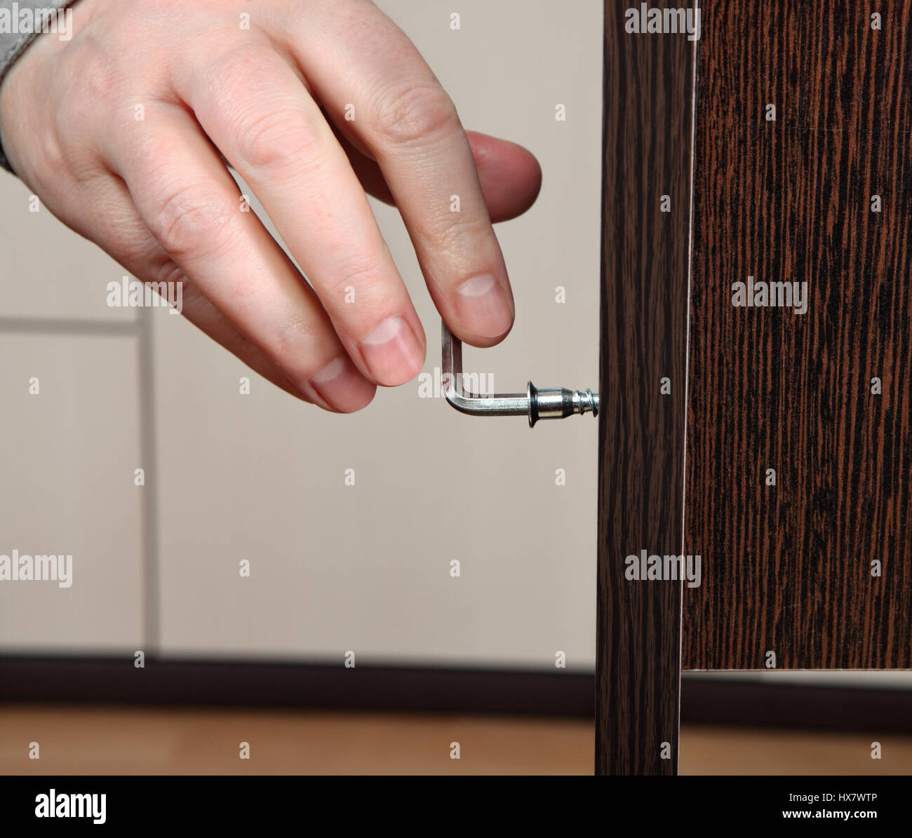 Closeup of a hand screw screwed Allen key, assembling furniture. Two board chipboard color dark brown wenge wood - Stock Image
