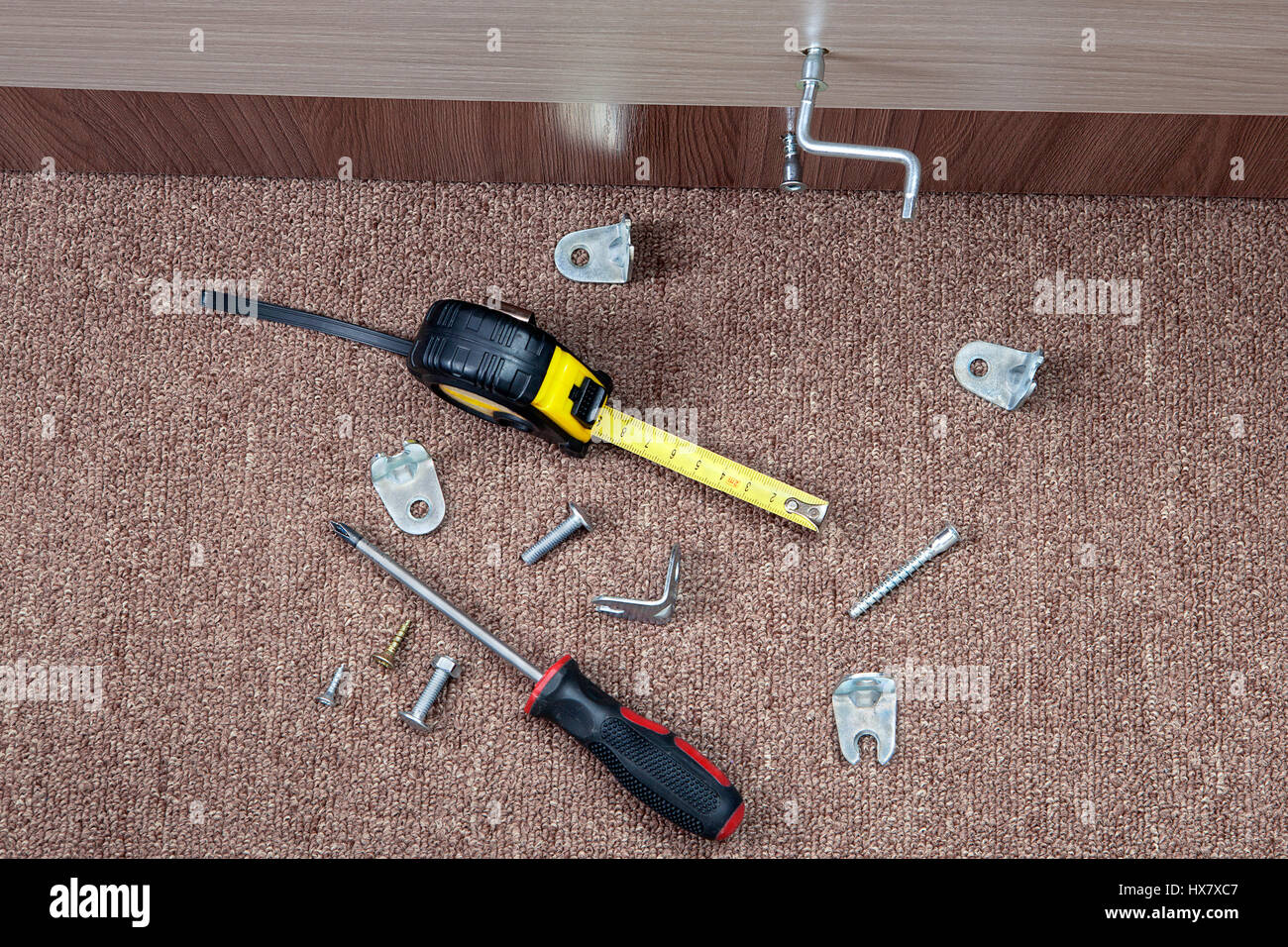 Steel fasteners, brackets and hand tools to install furniture. - Stock Image