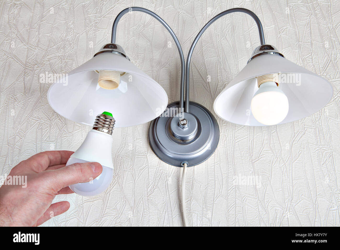 Replacing The Electric Light Bulbs In A Household Wall Lamp, LED Light Bulb  In Human Hand, Close Up.