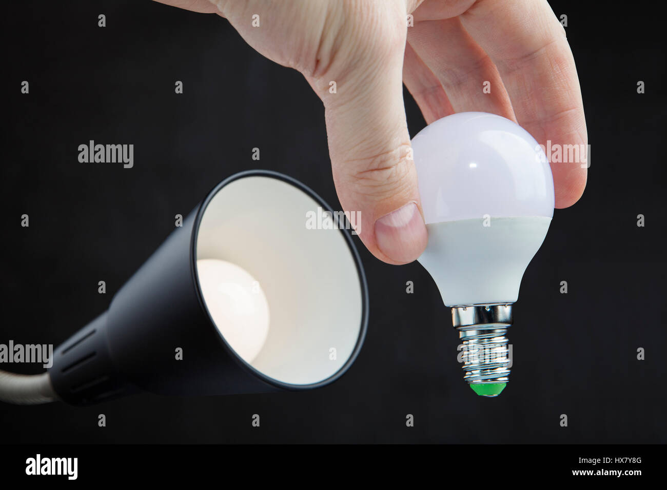 Hand holds a led lamp low energy consumption the exchange of light hand holds a led lamp low energy consumption the exchange of light bulbs in floor lamp dark background aloadofball Gallery