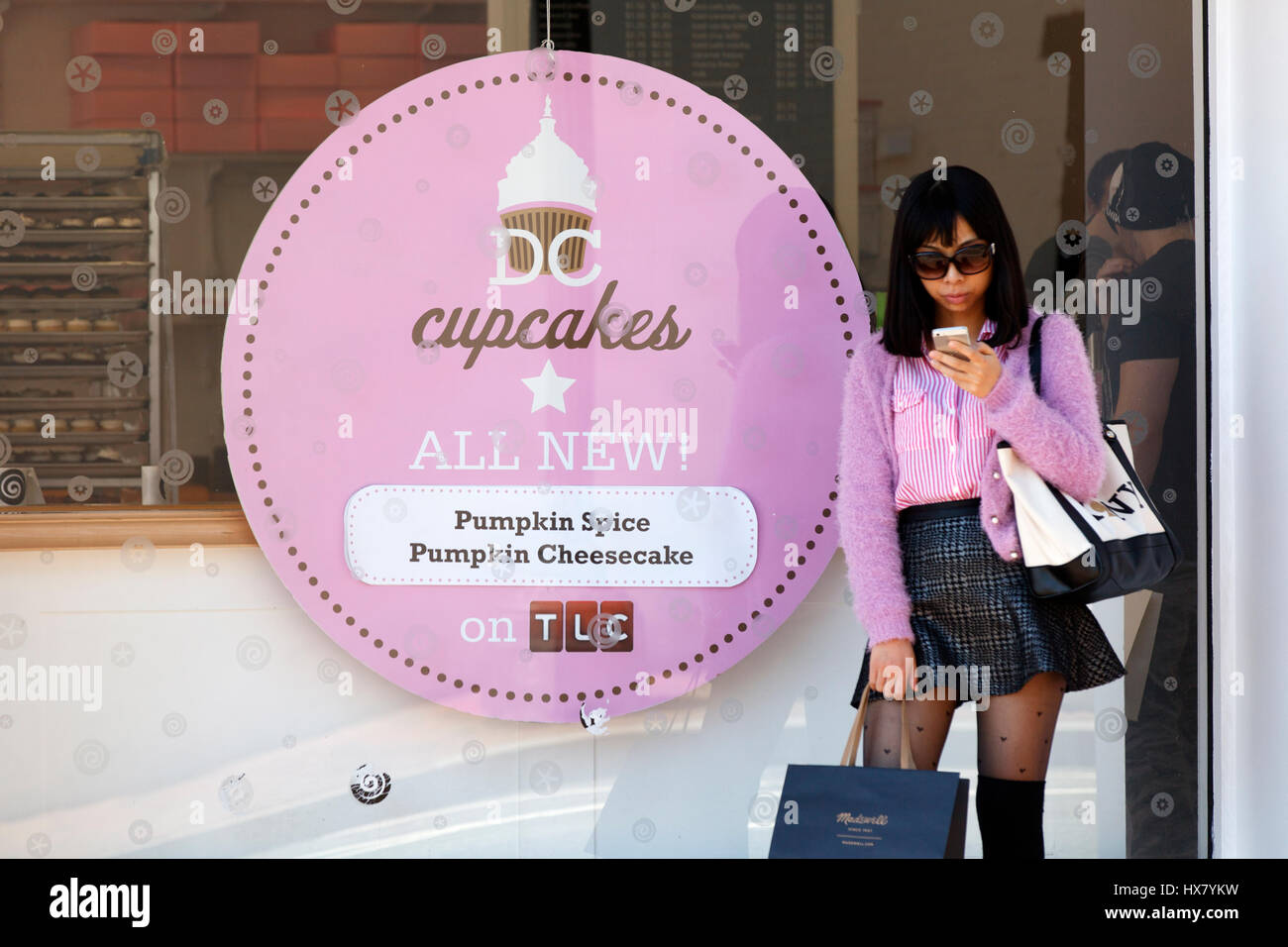A picture of the outside of Georgetown Cup Cakes in Washington DC. A customer waits outside the shop and is using - Stock Image