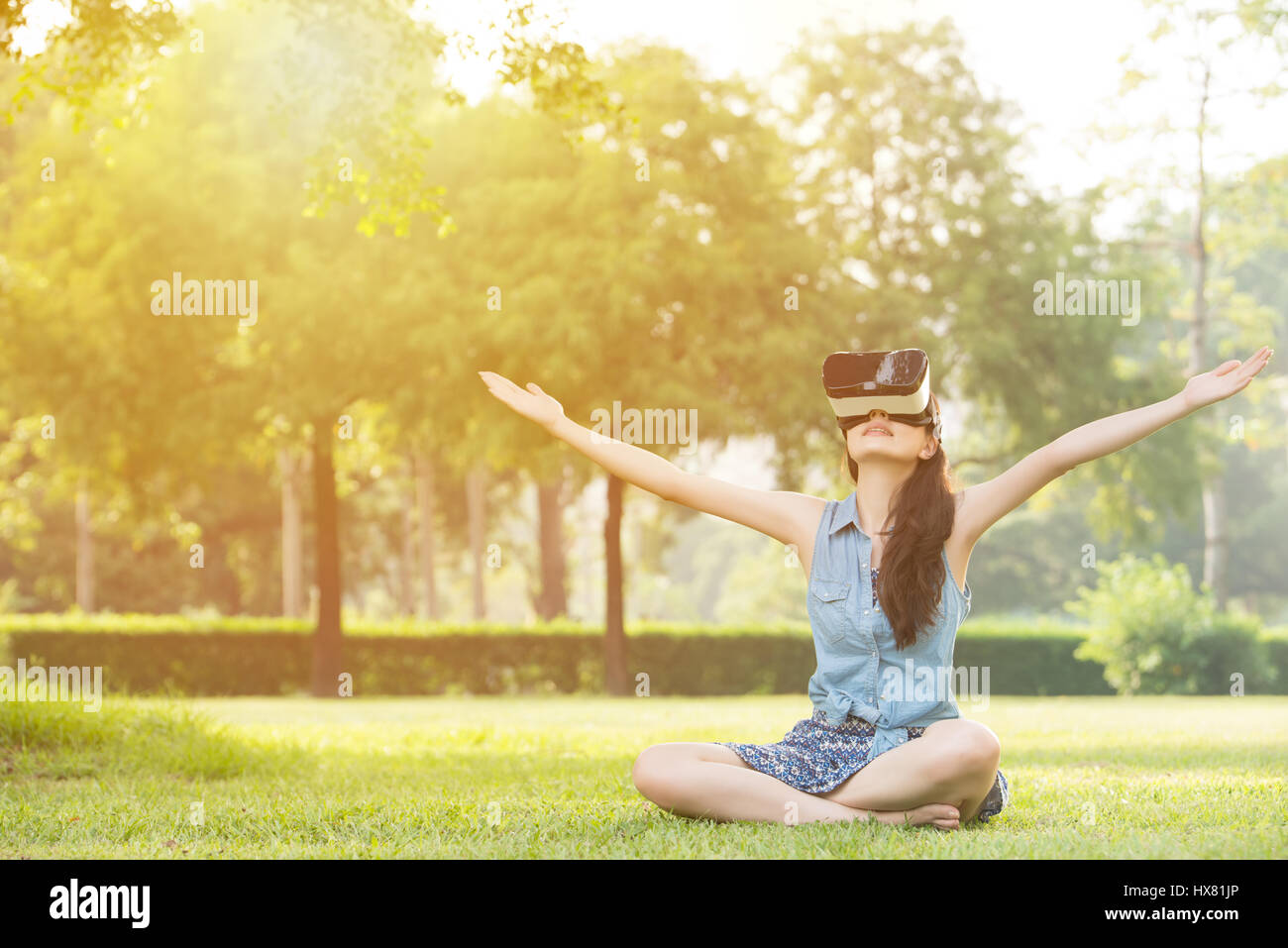 30d049bdbd beautiful asian woman enjoy virtual reality sitting on grass in outdoor  park. VR headset glasses device. nature outdoors background. people and  techno
