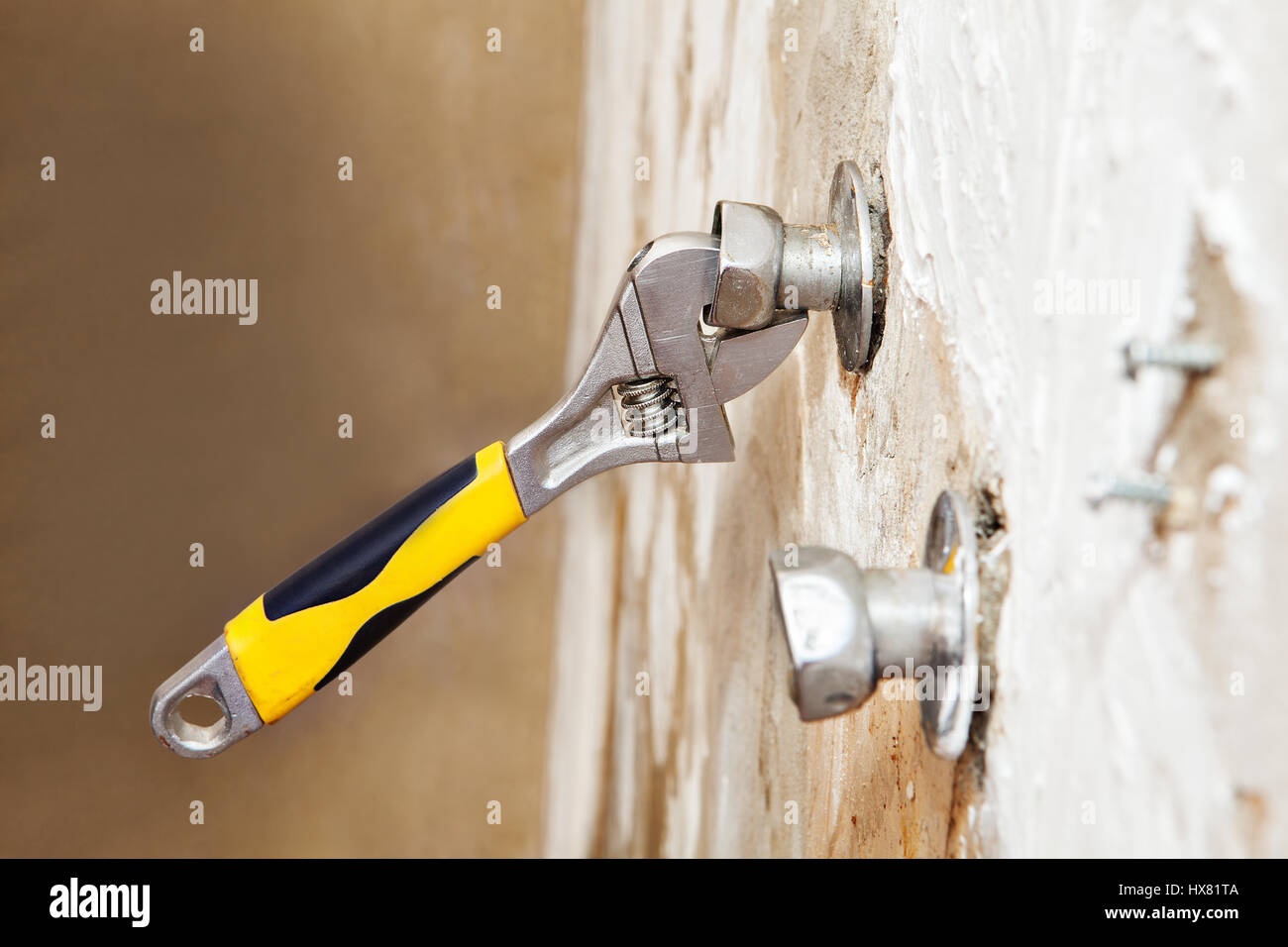 Closeup wall mount faucet eccentric adjusts position with plumbers adjustable wrench. Stock Photo