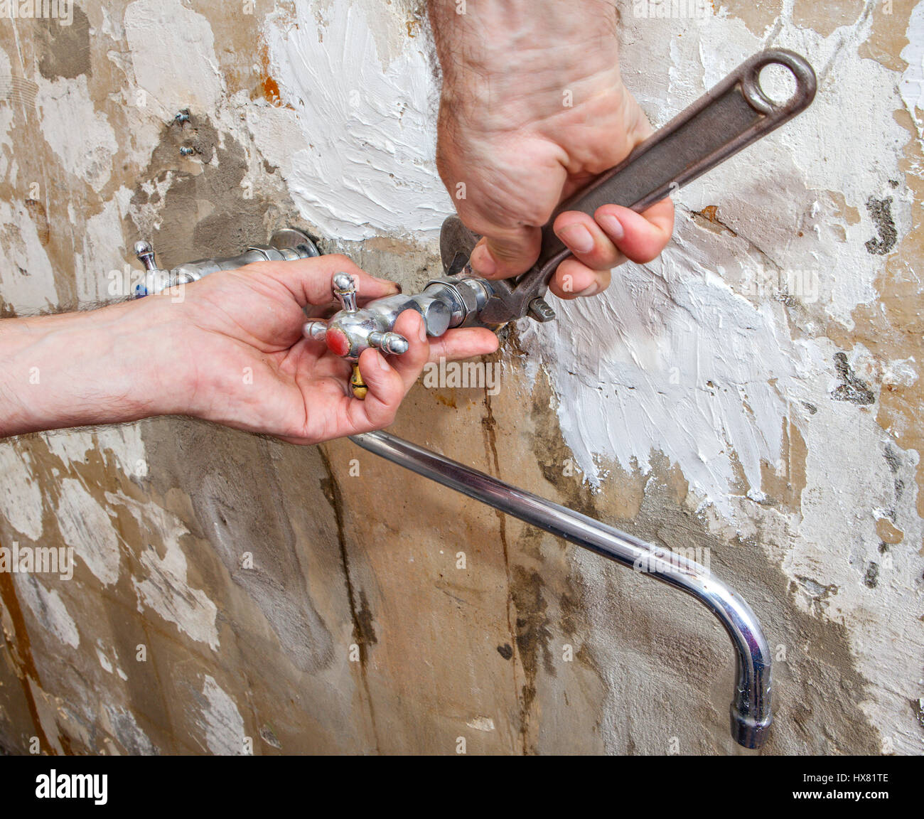 Dismantling of old faulty faucet, close-up hands of plumber with adjustable wrench. Stock Photo