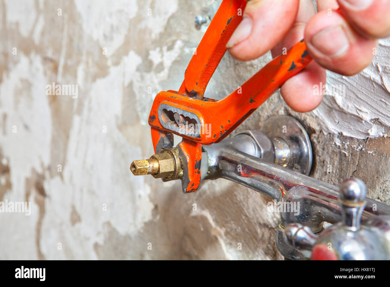 Plumber fixing water tap with leaking water users red plumber pliers ...