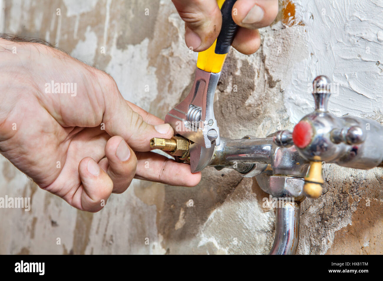 Kitchen faucet repair,  valve tap replacement, close-up adjustable wrench in hand plumbing. Stock Photo