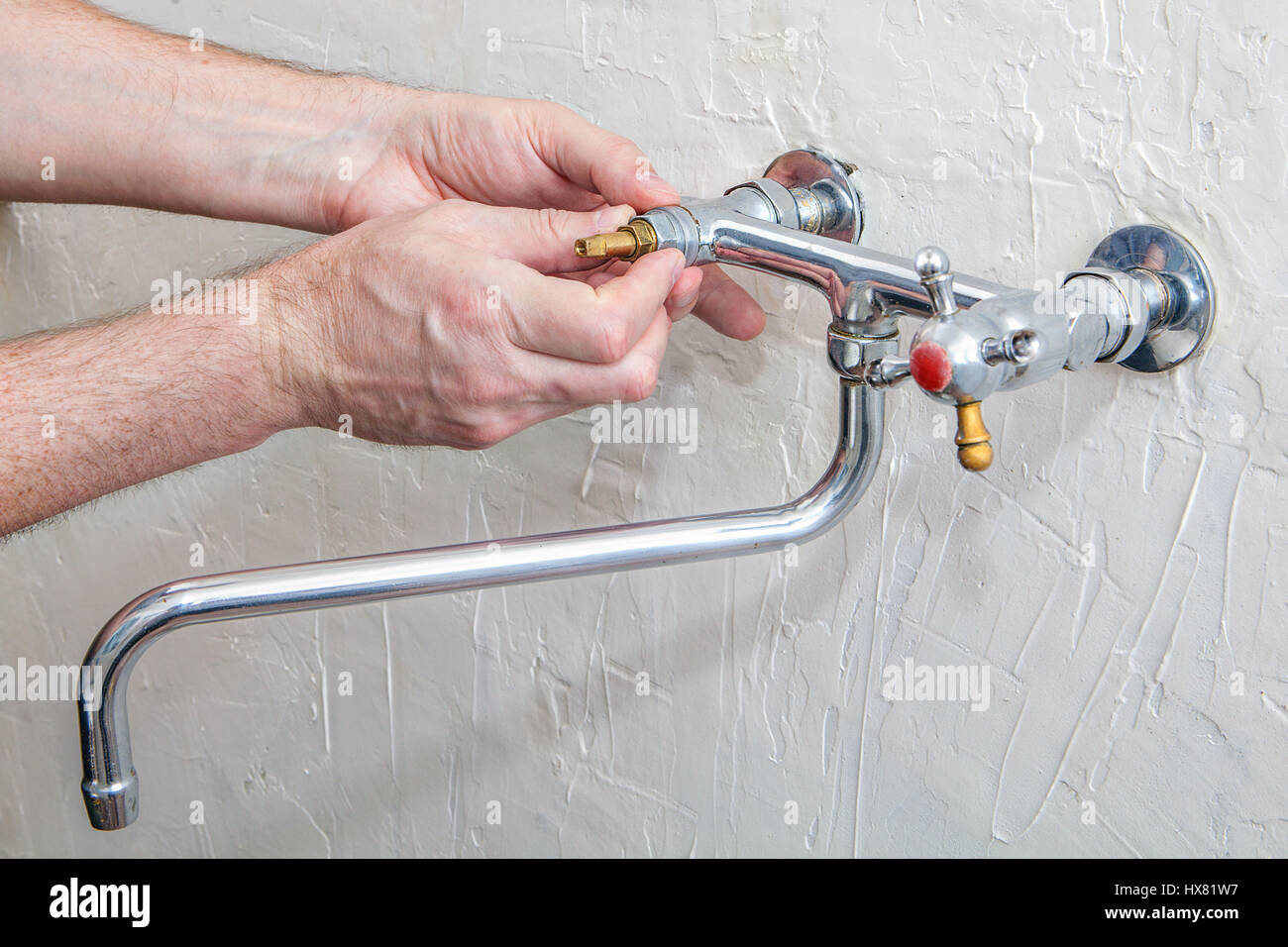 Plumber fixing water tap with leaking water, double handle kitchen ...