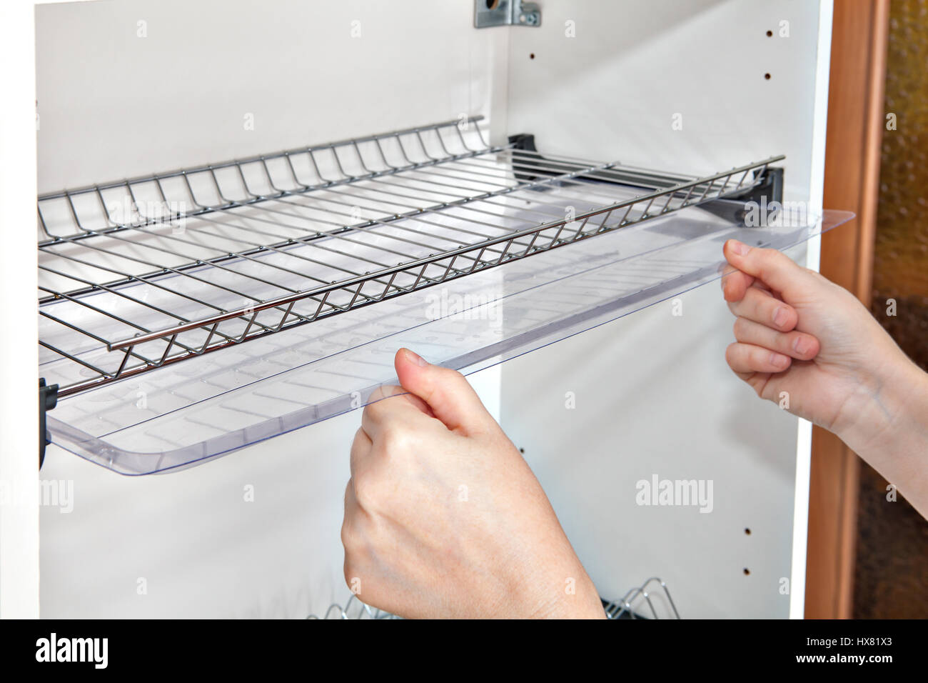 Installing shelf under kitchen cupboard with inside wire plate rack close-up of a woman hands holds drip tray. & Installing shelf under kitchen cupboard with inside wire plate rack ...