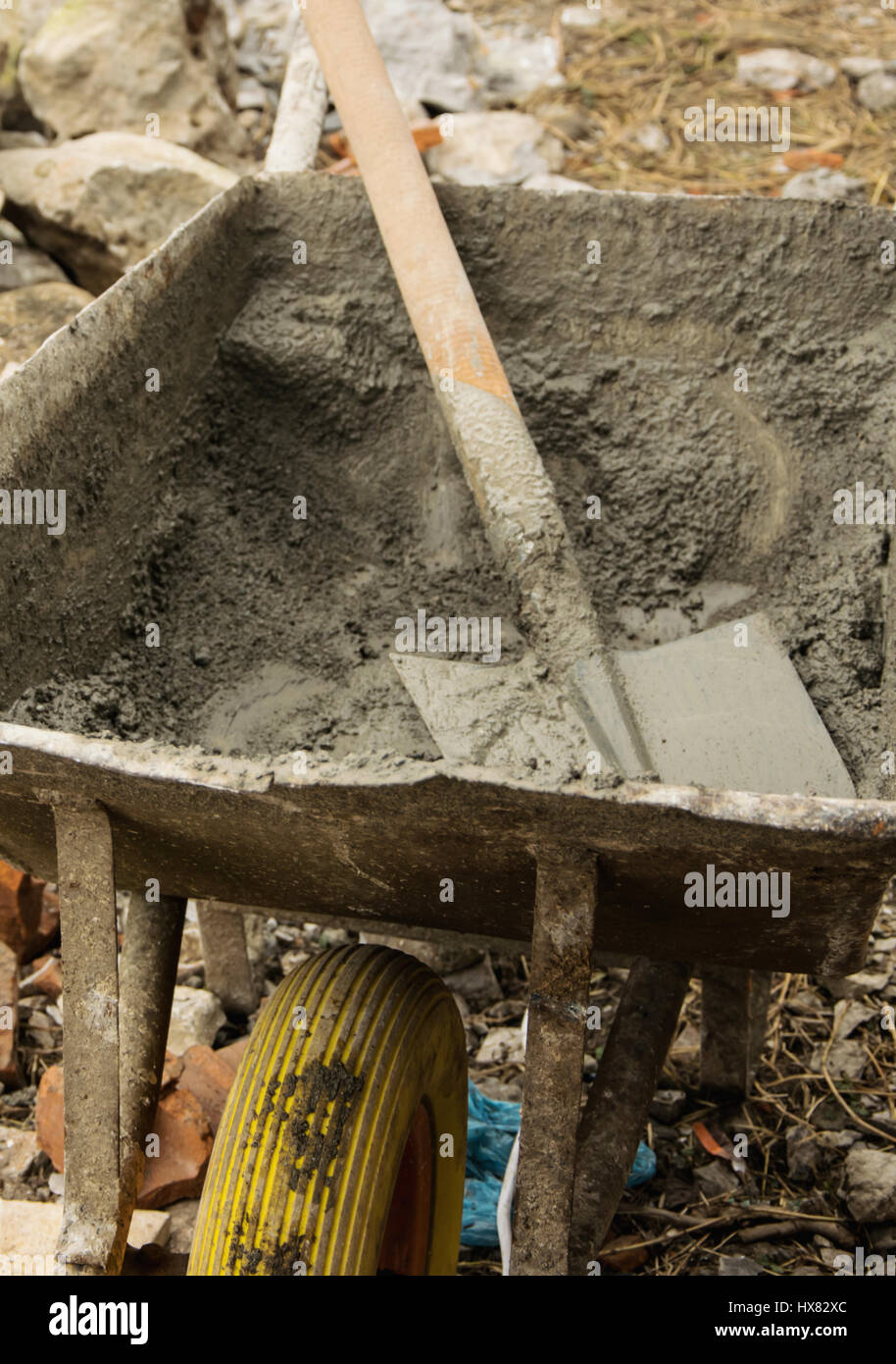Wheelbarrow with cement and shovel, on the yard work - Stock Image