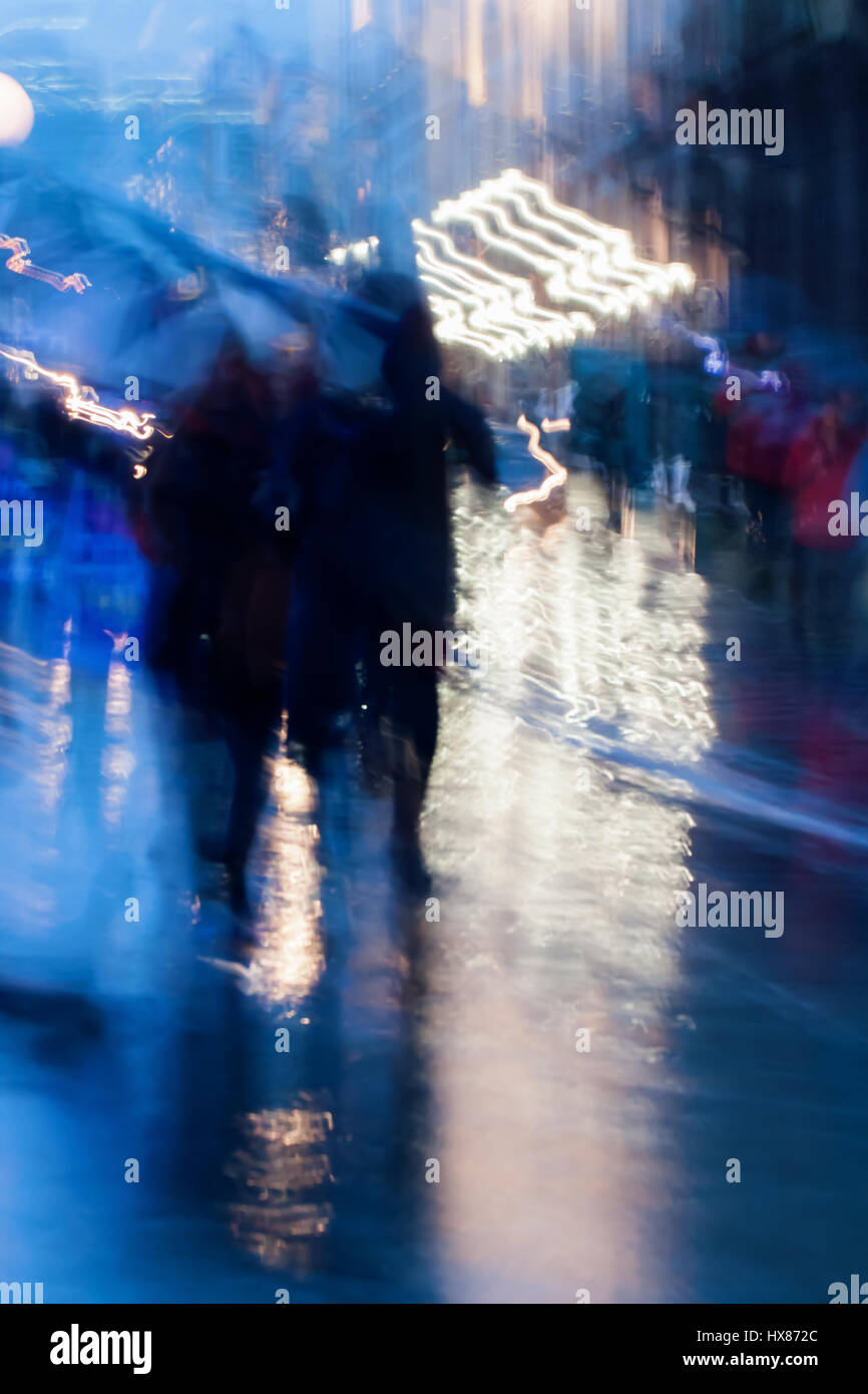 Abstract background in naturale blue tones. People walking down the city street in rainy evening. Intentional motion - Stock Image