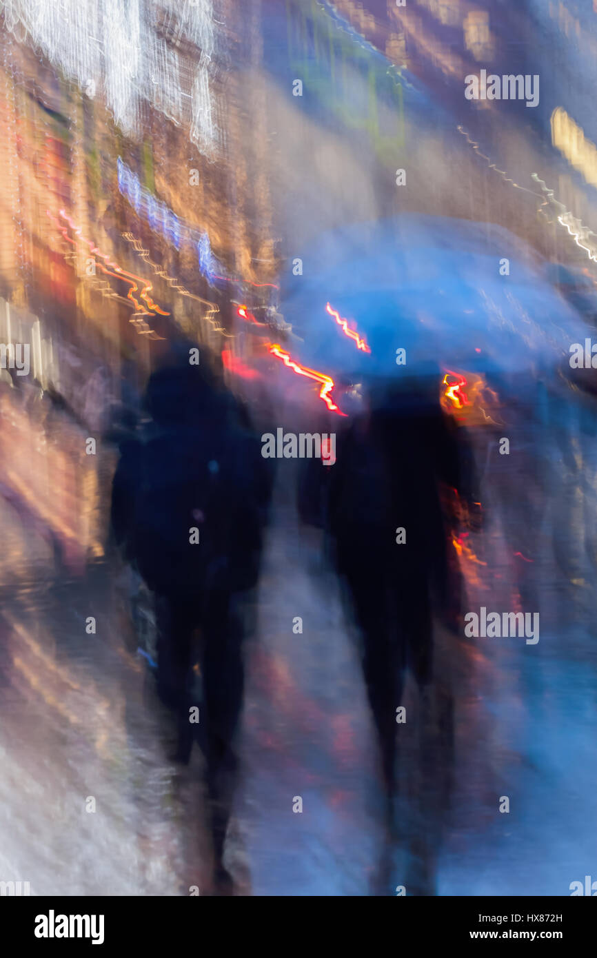 Abstract background of people hurrying down the city street in rainy evening, shop windows. Intentional motion blur. - Stock Image
