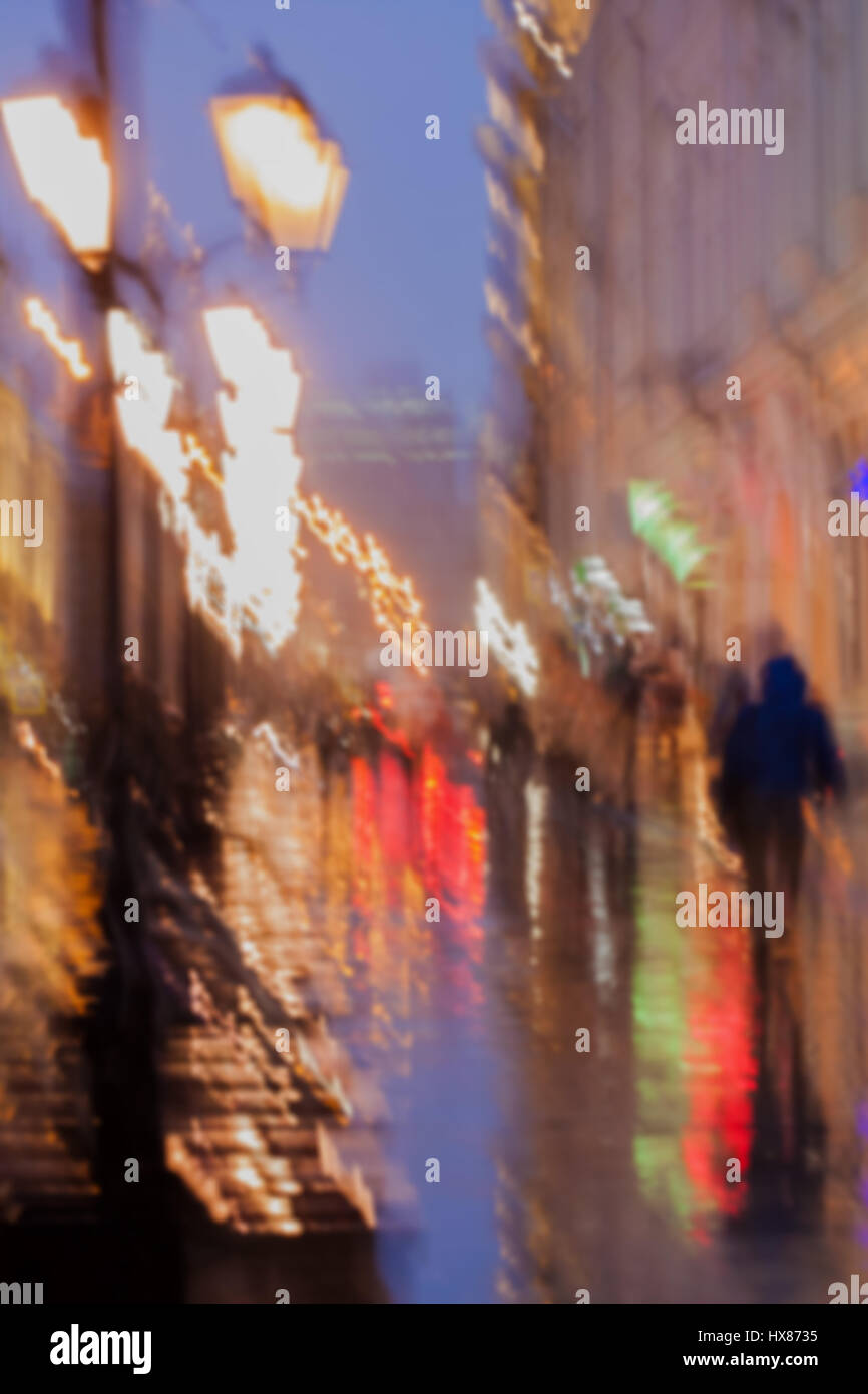 Abstract background of blurred young people walking down street in rainy evening, ipressionizm style, colorful light. - Stock Image