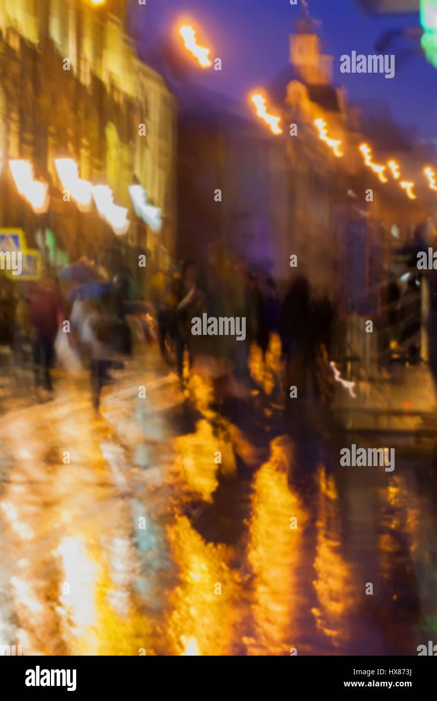 Abstract background of blurred people figures under umbrellas, city street in rainy evening, orange-brown tones - Stock Image