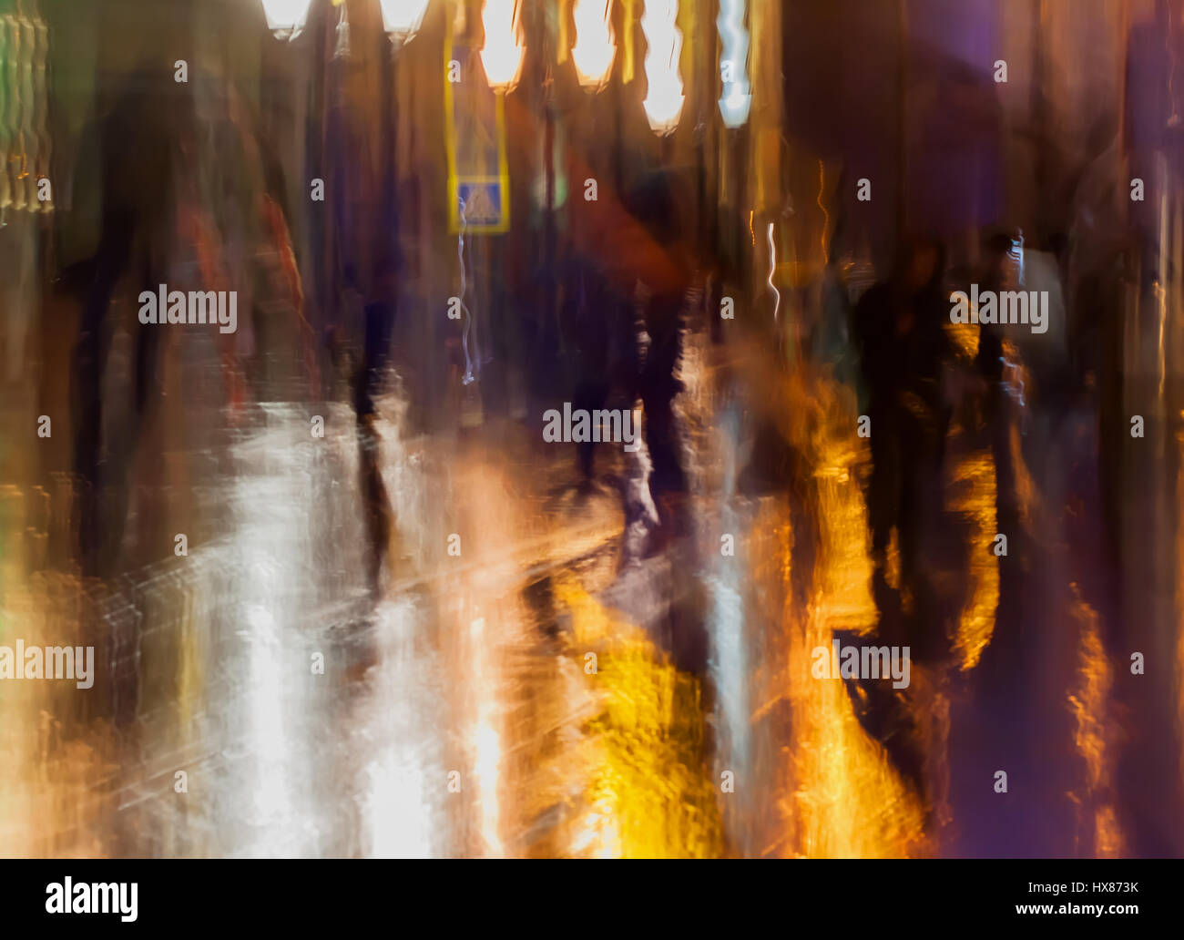 Abstract background of people figures, city street in rain, orange-brown tones. Intentional motion blur. Bright - Stock Image