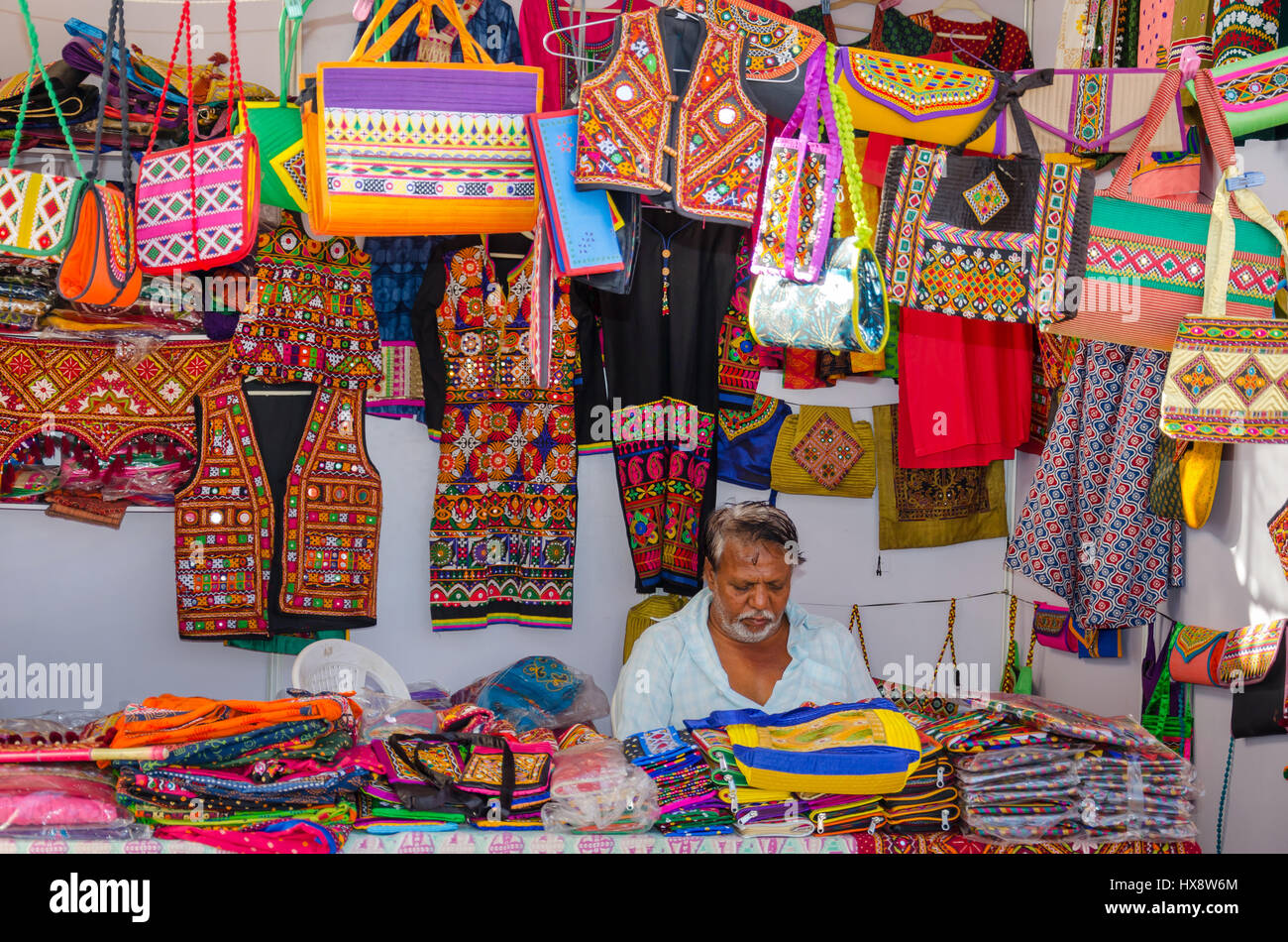 KUTCH, GUJARAT, INDIA - DECEMBER 27, 2016: An unidentified handicraft vendor in his traditional street shop selling - Stock Image