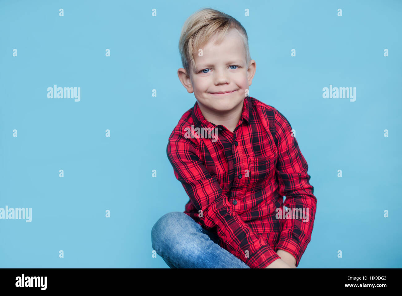 27e3646a6 Handsome little boy with red shirt. Fashion. Studio portrait over blue  background - Stock