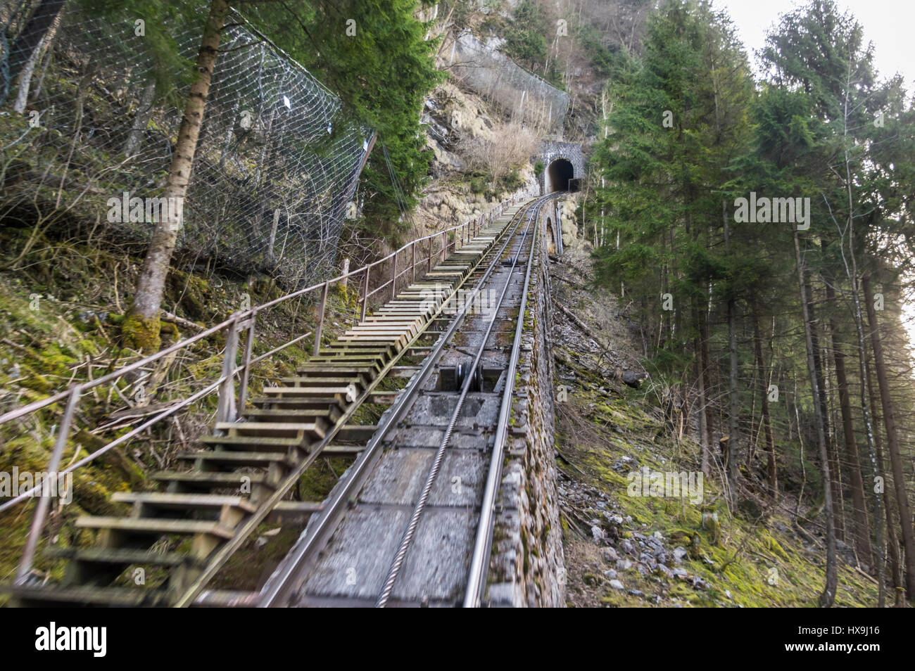 Railway tracks of the old Schlattli-Stoos funicular as seen during the ride. Pulling rope between the tracks. Schlattli, - Stock Image