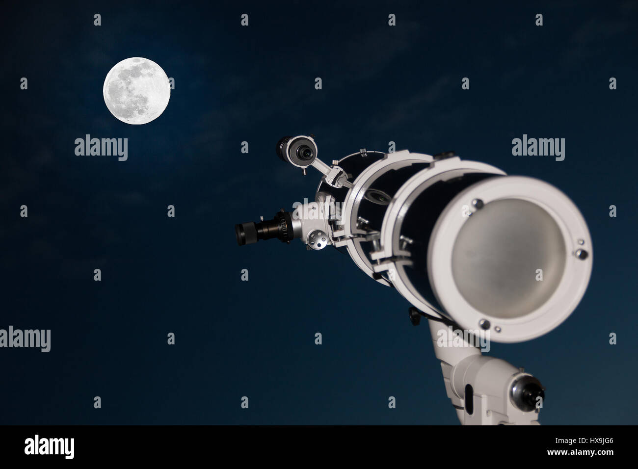 Astronomical telescope over dark sky with the moon in the night - Stock Image