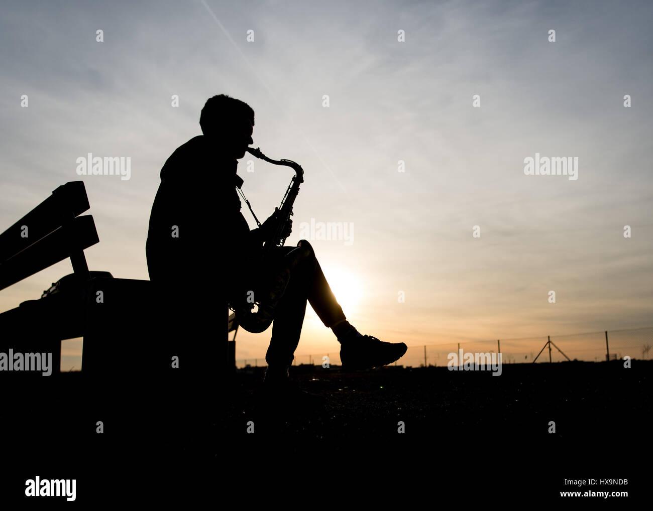 Berlin, Germany. 25th Mar, 2017. A man plays saxophone at sunset at Tempelhofer Feld (lit. Tempelhof Field) in Berlin, - Stock Image