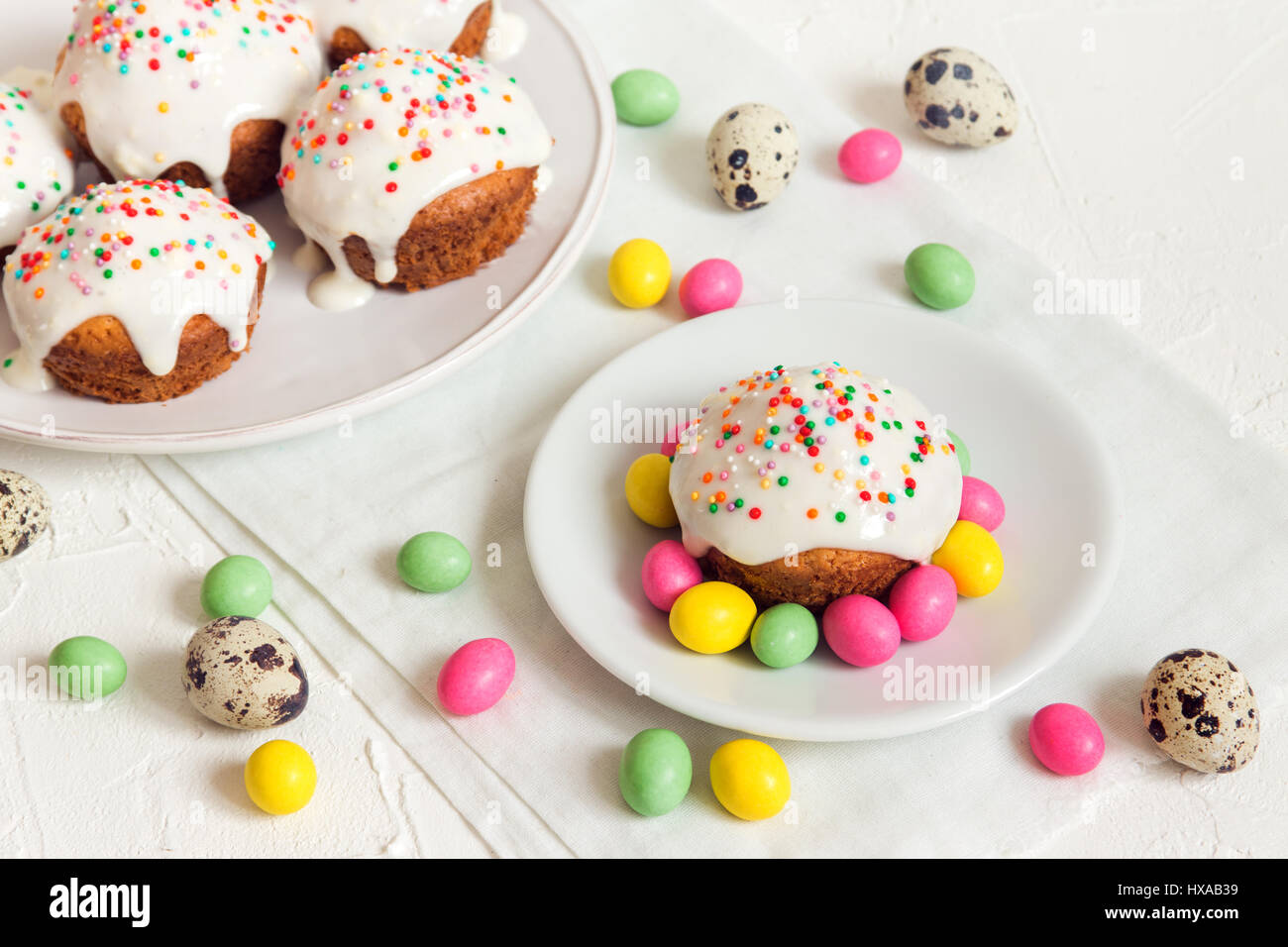 Easter cakes with white icing and easter festive decor on white background with copy space - homemade festive pastry - Stock Image