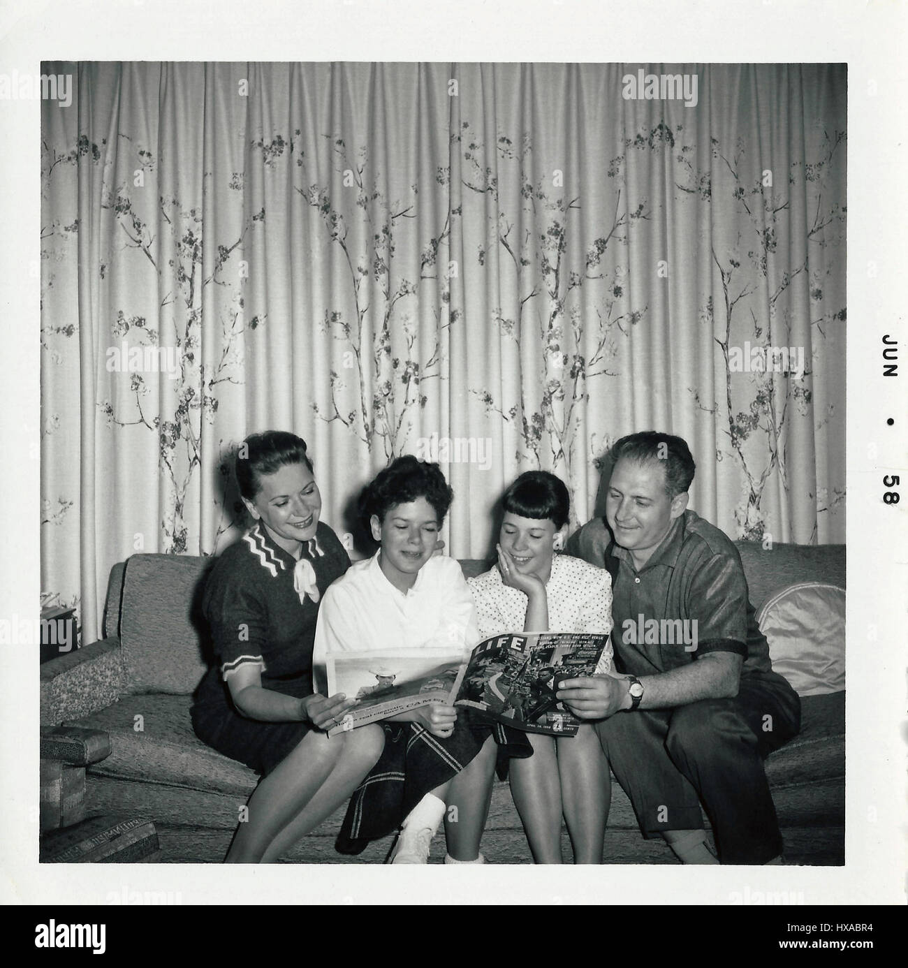 American family reading Life Magazine in 1958. - Stock Image