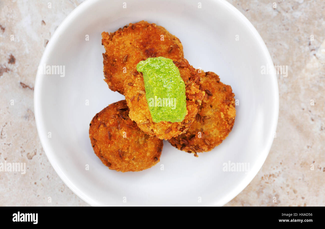 Middle east food -  bowl of Butternut Squash fritters and Zough relish - example of vegetarian food, seen from above - Stock Image