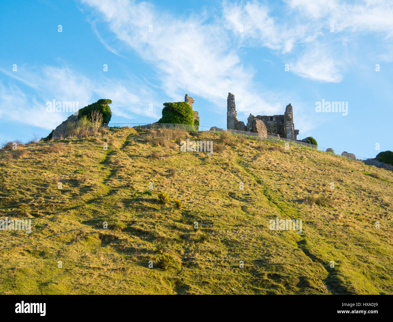 Wispy clouds and blue sky above the historic remainds of Corfe Castle, Corfe Castle, Dorset, UK - Stock Image