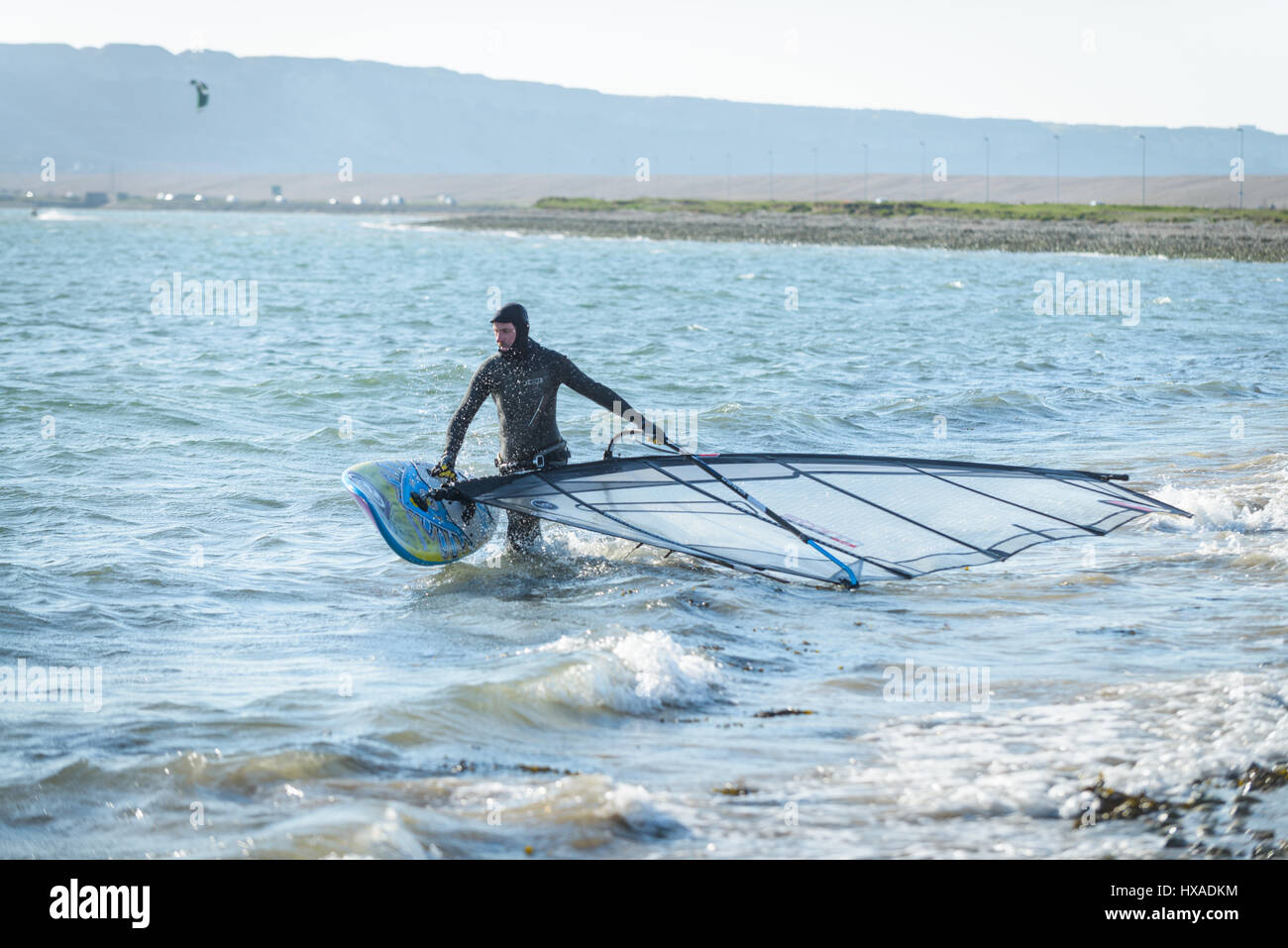 Portland Harbour, Dorset, UK. 26th March 2017. A man preparing his wind surfing board on a crisp windy sunny day - Stock Image