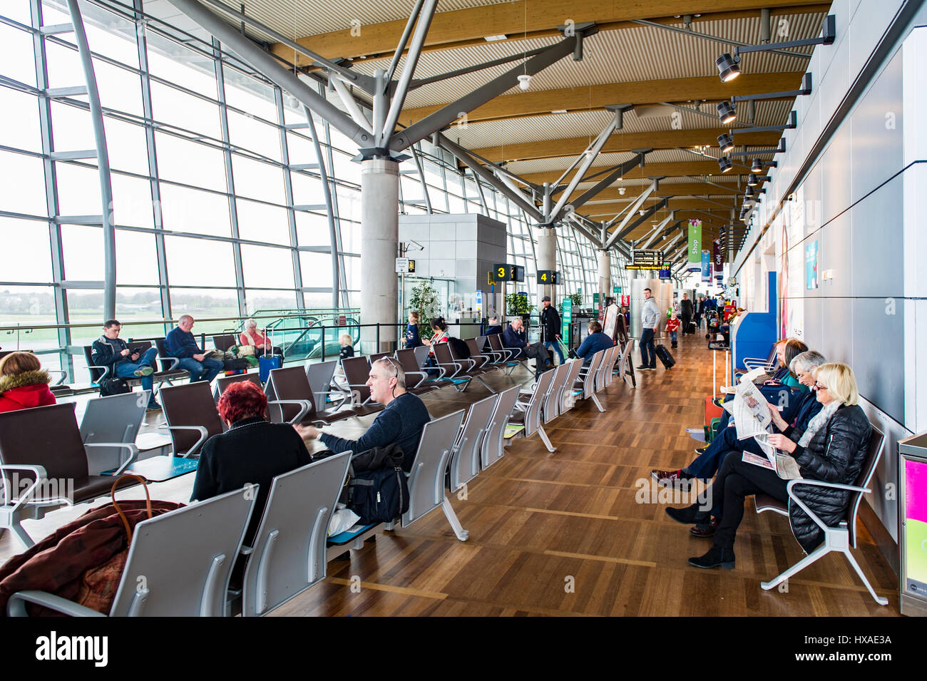 Departures lounge at Cork Airport, Cork, Ireland full of people waiting for their flights. - Stock Image