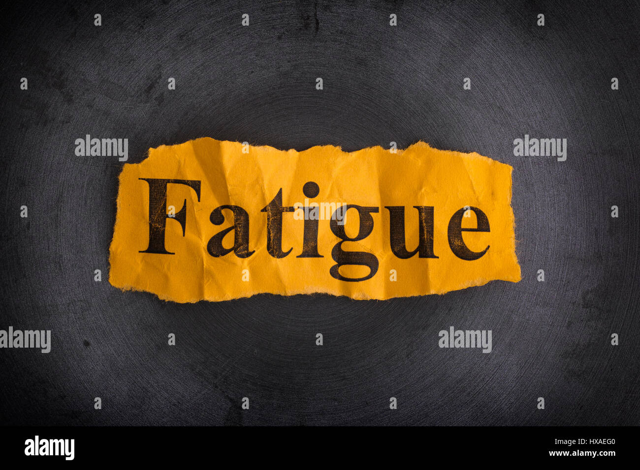 Crumpled piece of paper with the word Fatigue. Concept image. Close up. - Stock Image