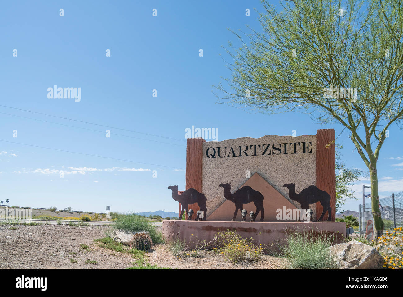 Quartzsite welcoming sign on the town limits made out of stone with three metal camels on the front portion of the - Stock Image