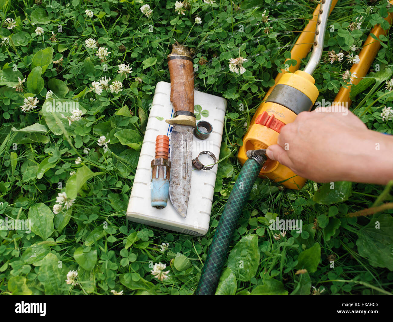 Male Hand Fixing A Garden Hose Laid On The Grass, Work Tools And Hose Clamps  Spread Out Around