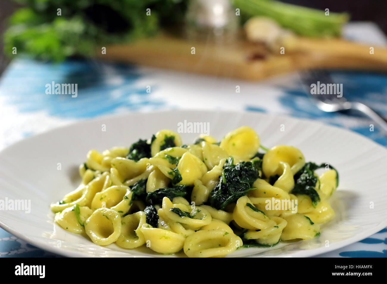 Turnip greens (collard greens) pasta (Italian Orecchiette alle cime di rapa) served in a white dish with fork on - Stock Image