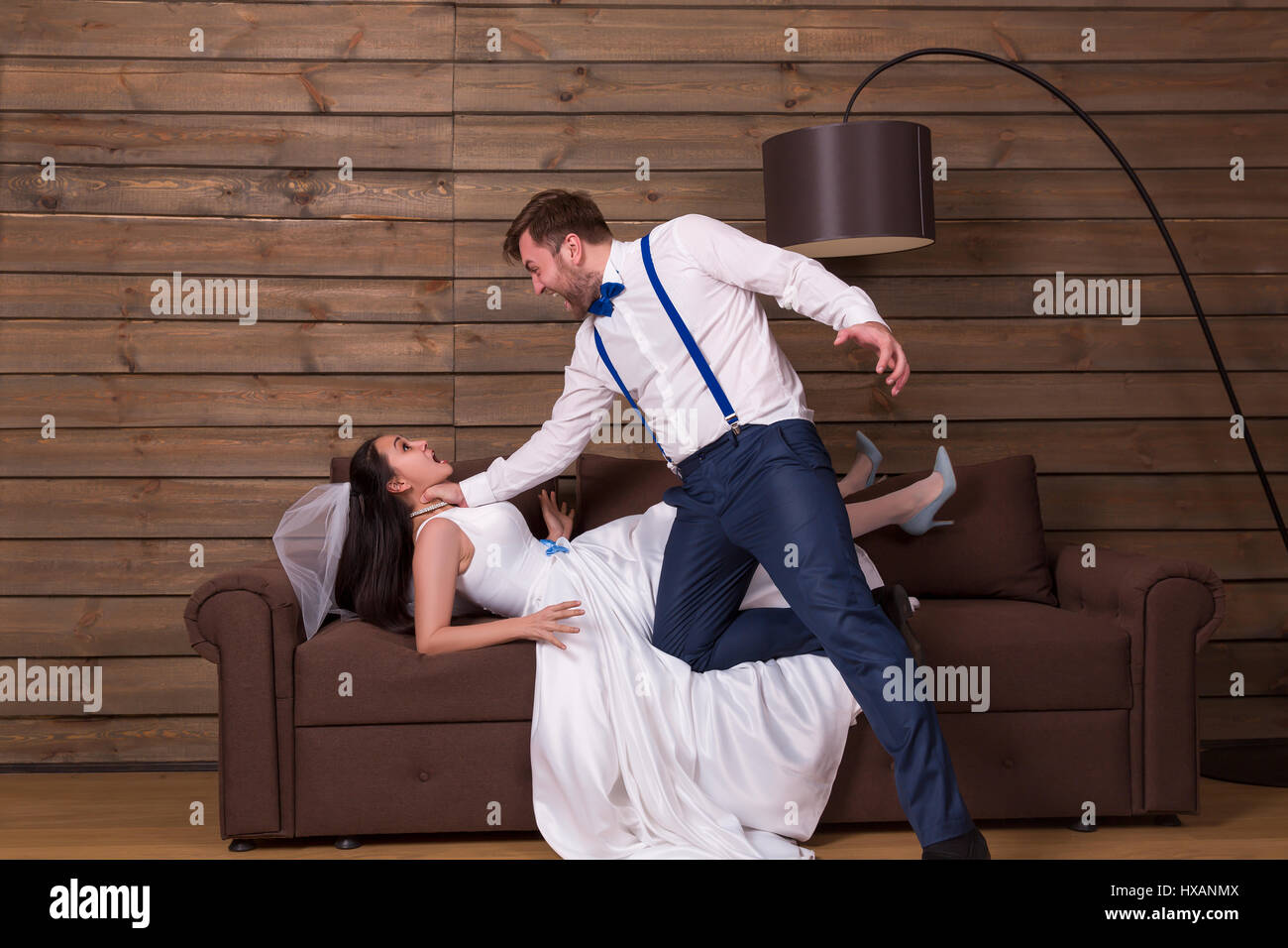 Groom trying to choke bride in white dress and veil, he shouting at her. Newlyweds complex relationship - Stock Image