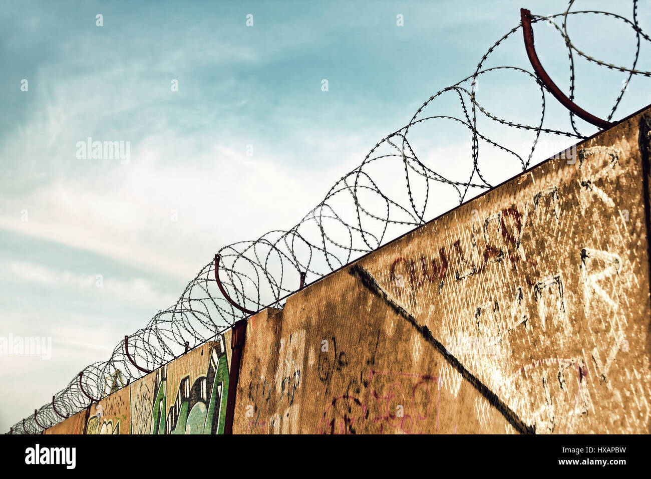Barbed wire fence detail against of the blue sky taken closeup.Toned image. - Stock Image