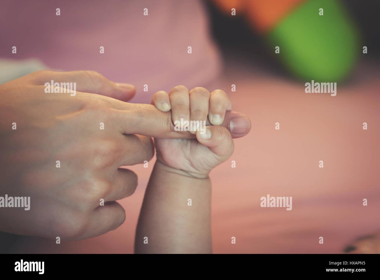 Newborn baby touching his mother hand Stock Photo