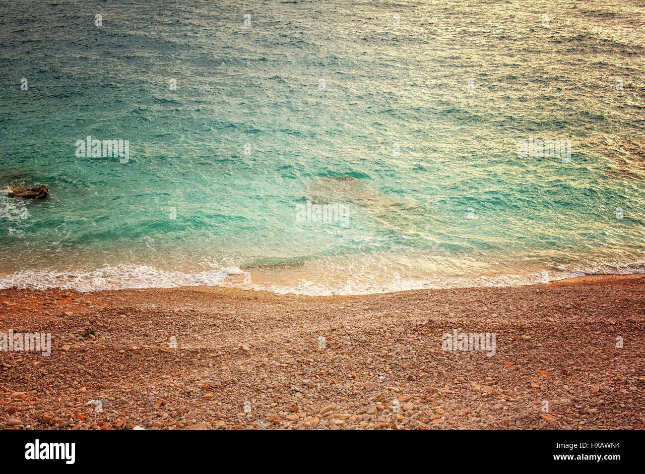 Sea and polished rocks on the shore closeup Stock Photo