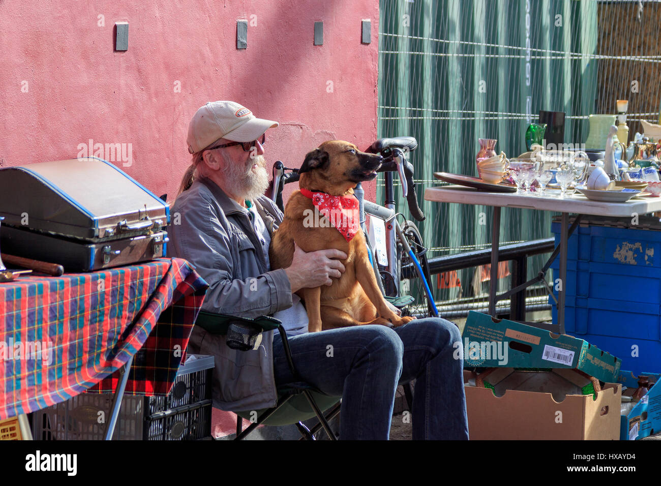 Stallholder at Glasgow's famous Barras open air and street market, sitting in the sun petting his dog. Glasgow. - Stock Image